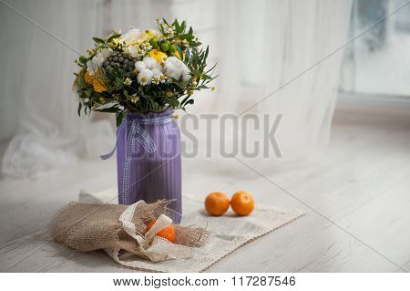 Wedding bouquet from cotton lemon chamomile on a green grass.