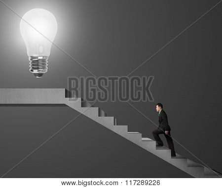 Businessman Climbing On Stairs To Glowing Bulb On Top