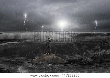 Man On Rock Gazing Lighthouse In The Ocean With Storm