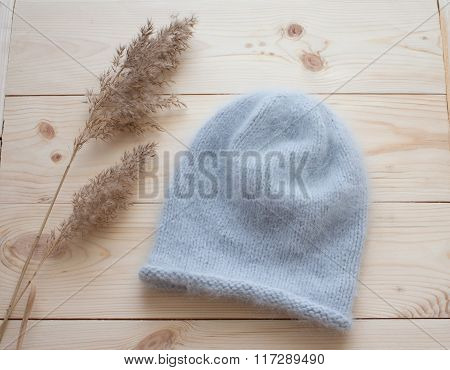 Soft Cap Of Blue Angora Bound By Hand On Natural Wooden Background