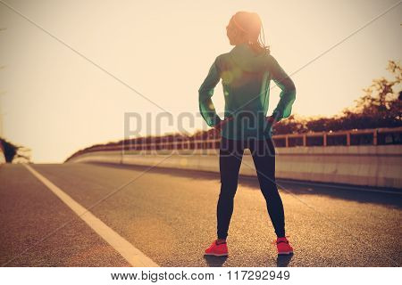 fitness young woman runner in sportswear standing with her hands on hips on sunrise road
