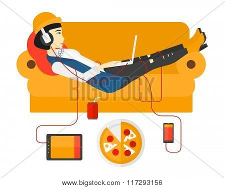 Woman with gadgets lying on sofa.