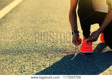 young sports woman runner tying shoelace on city road