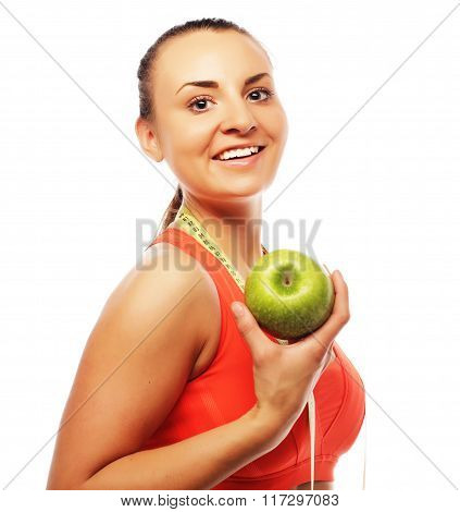 Young cheerful woman in sports wear with apple