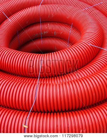 Red Rolled Up Wire Pipe On An Industrial Construction Site