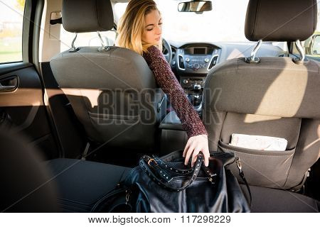 Woman reaching handbag from back seat