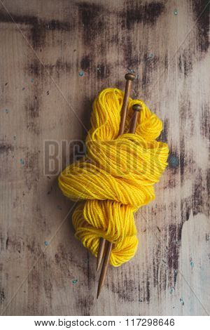 Skein of yellow yarn with knitting needles