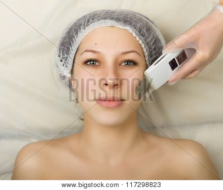 Beautician examining the face of a young female client at spa salon. ultrasonic cleaning person. Pro