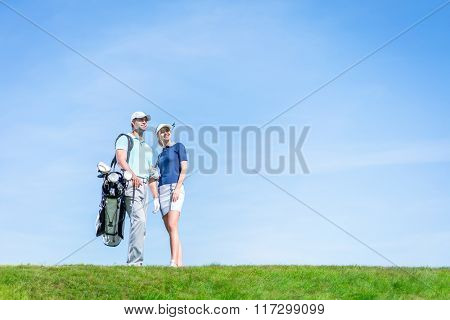 Young couple with a golf club outdoors