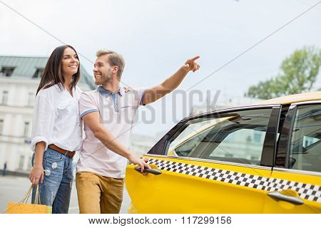 Young couple near a yellow taxi