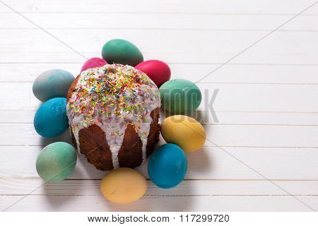 Colorful Easter Cake And Easter Eggs  On White Wooden Background.