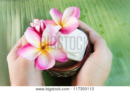 Hand Take Mini Set Of Bath Soap With Flowers Frangipani On Green Banana Leaf
