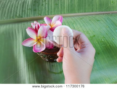 Hand Take Mini Soap  With Flowers Frangipani On Green Banana Leaf Background