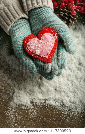 Female hands in blue mittens with decorative heart on snow background