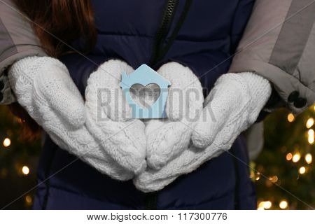 Hands holding tiny house with heart on lighted background