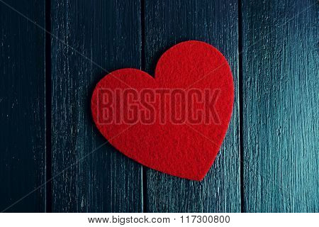 Red felt heart on purple wooden background