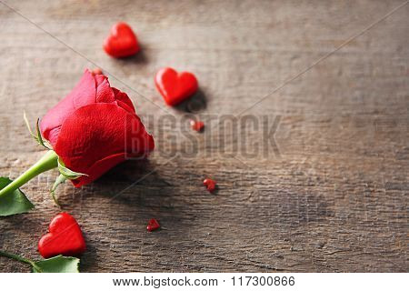 Beautiful rose with small hearts on wooden background