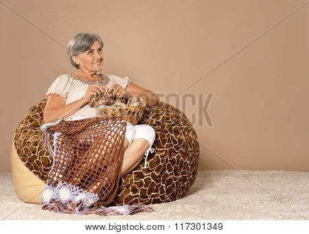 Senior woman knitting sitting in armchair