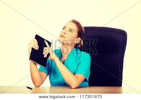 Young female doctor or nurse sitting behind the desk and thinking about something