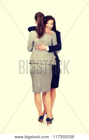 Two businesswomen embracing each other.