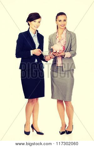 Two businesswomen with piggy bank.