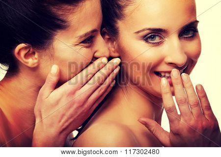 Two beauty women whispering.