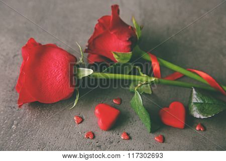 Beautiful red rose with small hearts on grey textured background