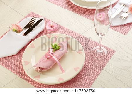 Table setting with dishes, cutlery, napkin and candles on pink background