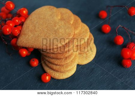 Heart shaped biscuits and ash berries on dark grey background