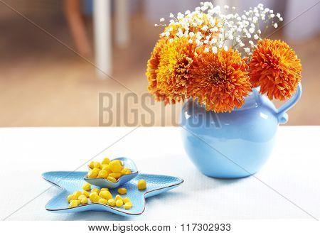 Vase of orange chrysanthemums on table