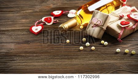 White wine bottle and gift box on wooden background