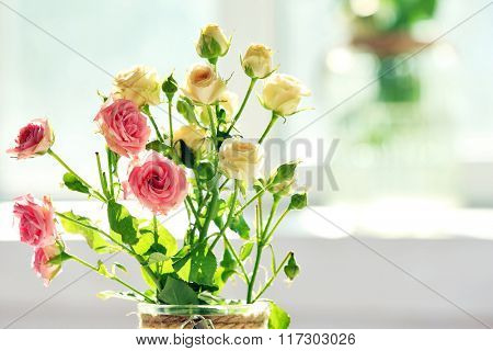 Beautiful spring flowers in vase on window background