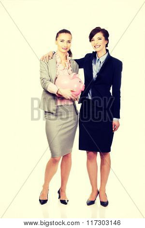 Two businesswomans with piggy bank.