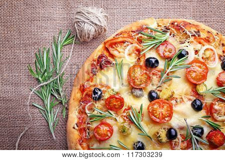 Delicious fresh pizza on sackcloth, top view