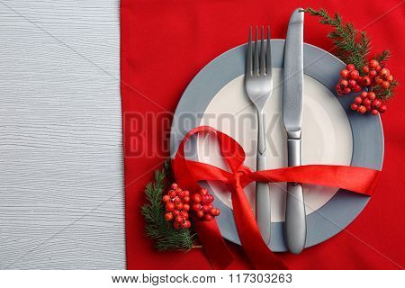 Christmas serving cutlery on plate and napkin over light wooden table, close up