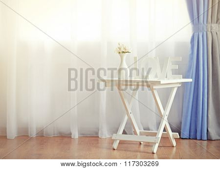 Little table in the room in front of window with curtains