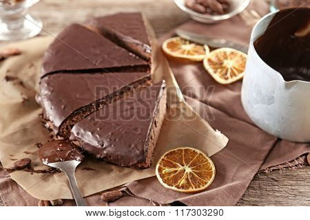 Sliced chocolate frosting cake on wooden table