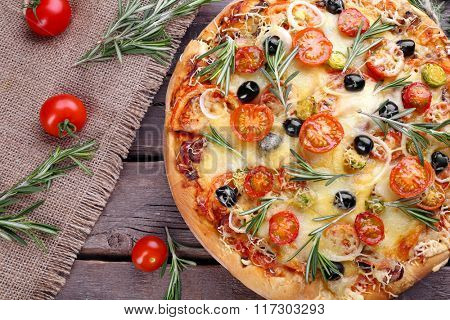 Delicious fresh pizza on wooden background