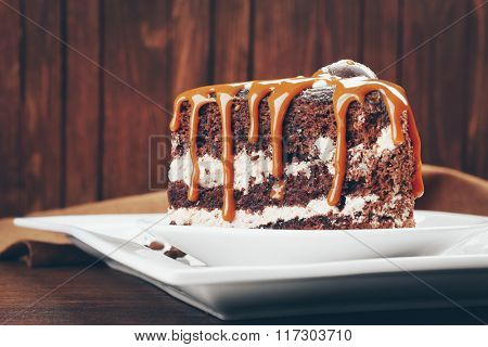 Piece of chocolate cake with caramel on wooden background