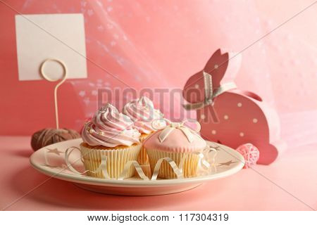 Few tasty cupcakes with decorations on pink background