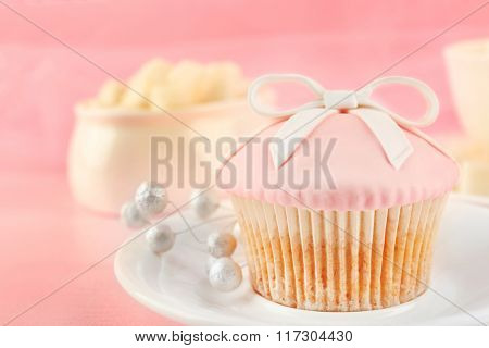 Tasty pink cupcake with decorations, closeup