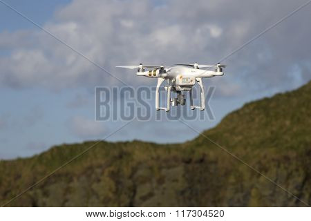 Small Unmanned Helicopter With A Camera Flying In The Blue Sky Above The Hills