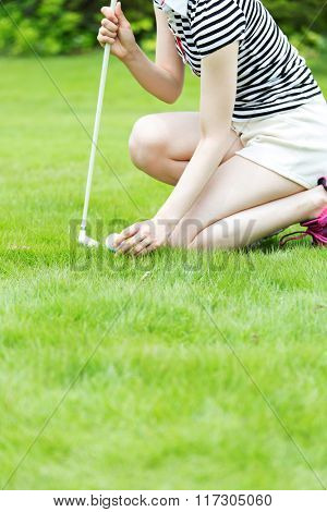 Close up of female golf player picking up ball from hole at green