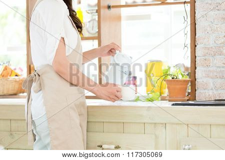 Portrait of young adult brunette asian woman making tea or green tea on kitchen room