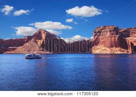 Walk on white boat on a sunny day. Scenic huge artificial water basin of the Colorado River, USA. Lake Powell is surrounded by magnificent sandstone hills