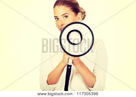 Beautiful businesswoman screaming through megaphone