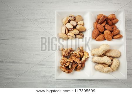 Walnut kernels, almonds, pistachios, peanuts in the ceramic rectangle plate on the wooden table