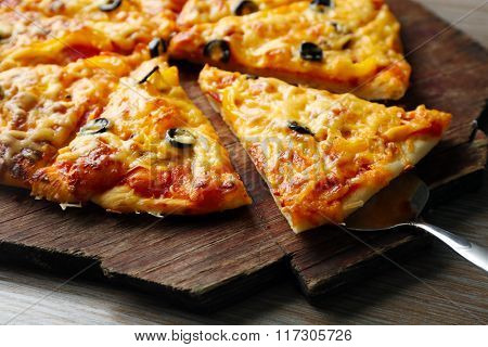 Delicious sliced pizza on wooden board, close up