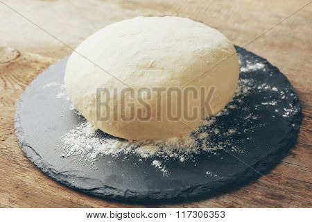 Fresh prepared dough on a wooden board, close up