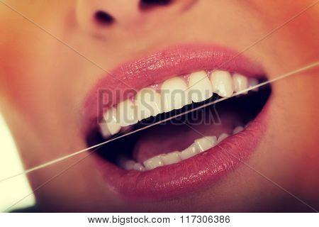 Woman using dental floss.